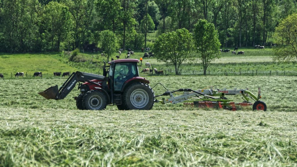 red tractor with farming attachment on field during daytime